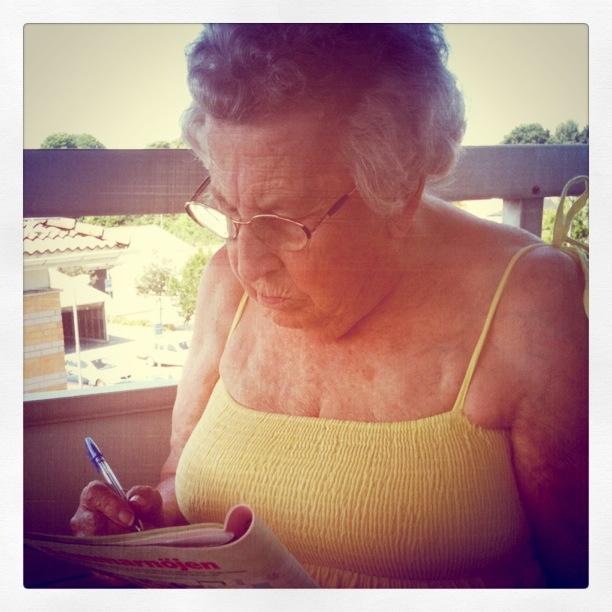 Mormor med korsord på balkongen