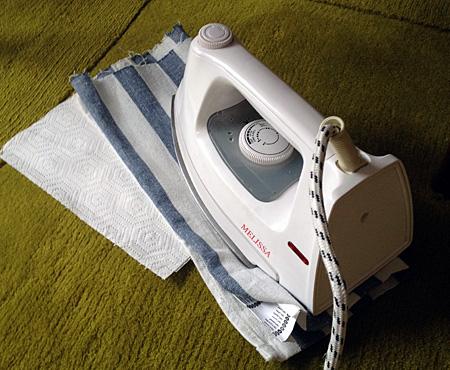 Fyra lager hushållspapper, en tunn handduk och så strykjärnet ovanpå för att smälta stearinet och suga upp det