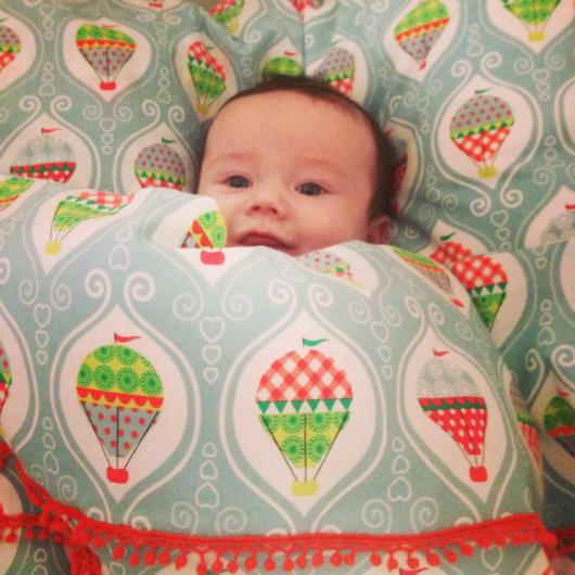 Nöjd bebis i fina sängkläder i spjälsängen
