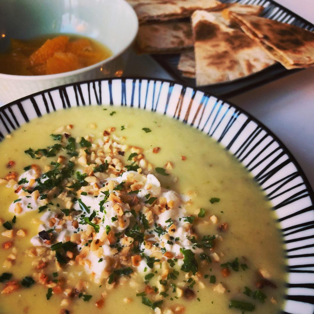 Soppa i en randig skål, ett randigt fat med tillagat bröd, och en skål med apelsinskivor utan hinnor