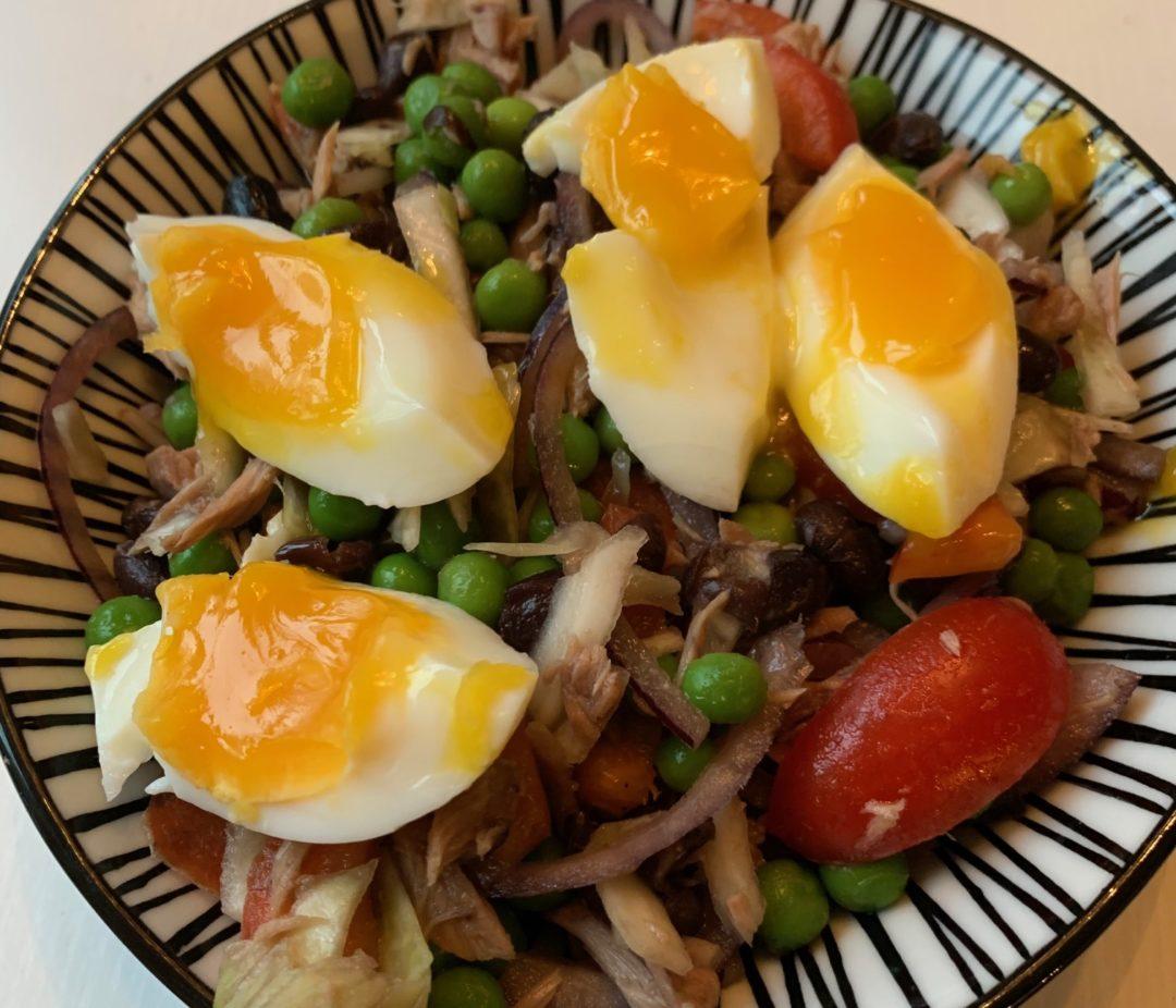 tonfisksallad i en svartvitrandig skål med kokt ägg i klyftor på toppen